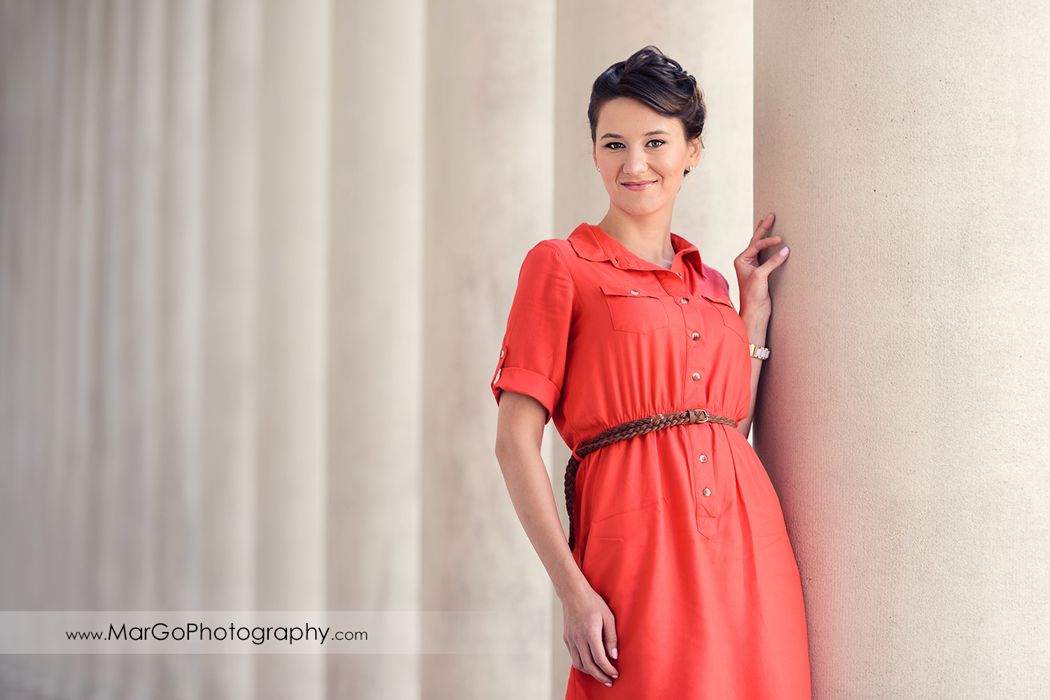 3/4 portrait of woman in red dress standing next to white columns during engagement session at San Francisco Legion of Honor