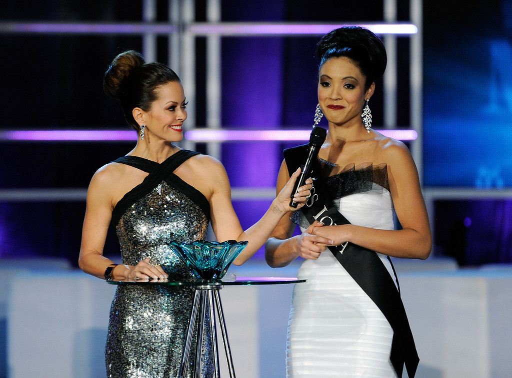 . Host Brooke Burke Charvet (L) holds a microphone for Mariah Cary, Miss Iowa,  as she answers a question during the interview portion at the 2013 Miss America Pageant at PH Live at Planet Hollywood Resort & Casino on January 12, 2013 in Las Vegas, Nevada.  (Photo by David Becker/Getty Images)