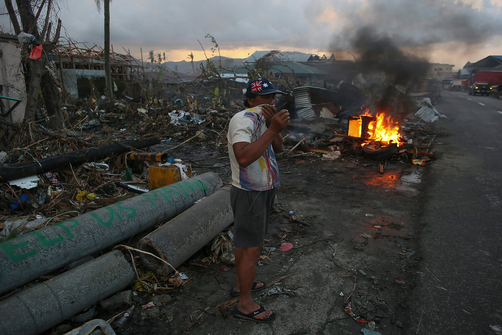. A Filipino typhoon victim burns debris at sunset in the super typhoon devastated city of Tacloban, the Philippines, 21 November 2013.   EPA/NIC BOTHMA