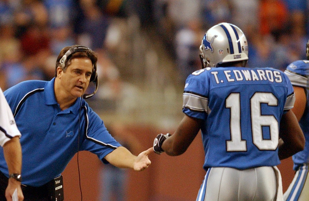 . Lions head coach Steve Mariucci shakes the hand of Troy Edwards (16) after picking up a key first down  against the Arizona Cardinals during Sunday\'s game at Ford Field in downtown Detroit.