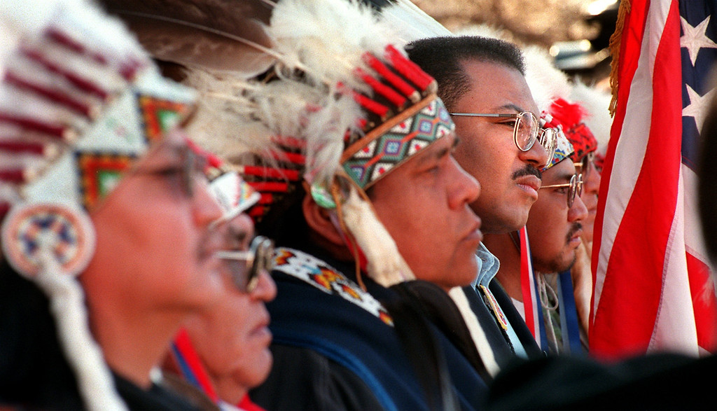 . [sandcreek 8]  Caption: Lt. Gov. Joe Rogers (4th from left), is surrounded by  leaders and elders of the Northern Cheyenne Tribe as he listens  to other speakers addressing the crowd gathered for the 135th  anniversary of the Sand Creek Massacre Monday morning on the west  steps of the State Capital in Denver, Colorado on November 29, 1999.  Runners took part in a 170 mile spiritual healing run from the  site of the massacre to the Capital. (LEW SHERMAN/THE DENVER POST)