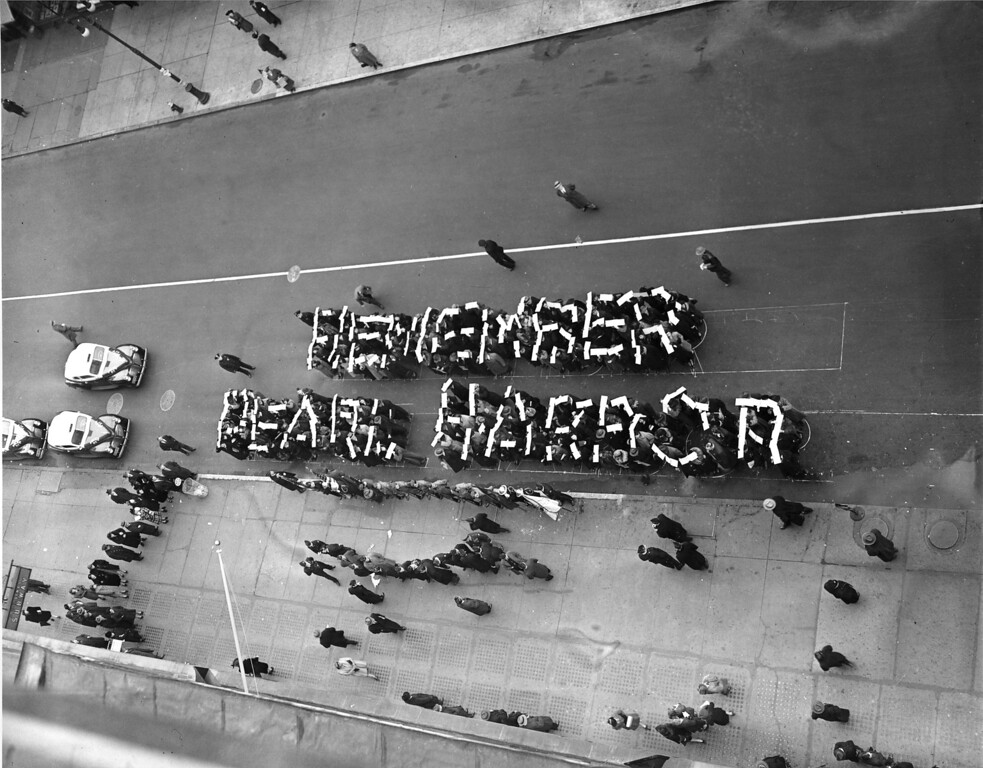 ". Members of the Hearns Volunteer National Defense Corps spell the slogan ""Remember Pearl Harbor\"" at a rally held on 14th St. between Fifth and Sixth Avenues in New York City, Dec. 27, 1941.  (AP Photo)"