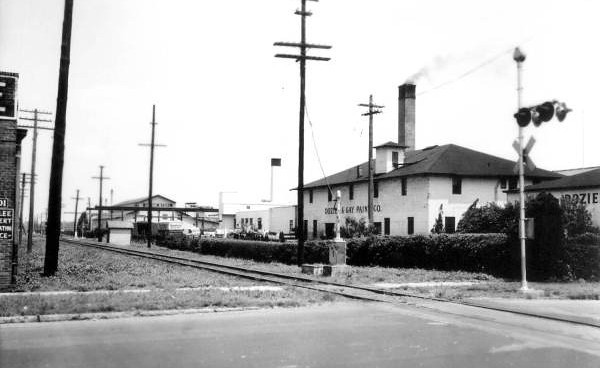 The Dozier and Gay Paint Company in 1944. The southwest corner of the Kelly Furniture Company can be seen to the left.  Today, the S-Line Greenway has replaced the railroad and the paint company has been demolished and is used as a parking lot for the Kelly Furniture Company building. Courtesy of the State Archives of Florida, Florida Memory, http://floridamemory.com/items/show/52862