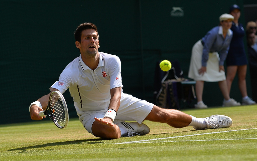 . Serbia\'s Novak Djokovic dives as he returns against Argentina\'s Juan Martin Del Potro during their men\'s singles semi-final match on day eleven of the 2013 Wimbledon Championships tennis tournament at the All England Club in Wimbledon, southwest London, on July 5, 2013. CARL COURT/AFP/Getty Images