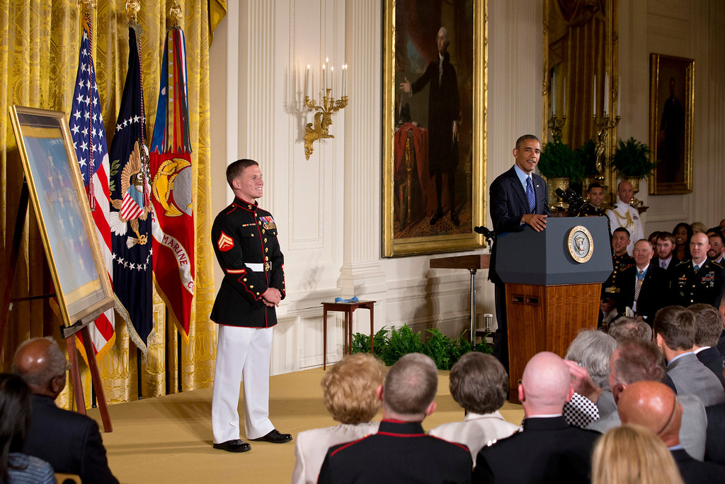 ". President Barack Obama speaks in the East Room of the White House in Washington,  Thursday, June 19, 2014, during a ceremony where he awarding retired Marine Cpl. William ""Kyle\"" Carpenter, 24, left, the Medal of Honor for conspicuous gallantry.  (AP Photo/Jacquelyn Martin)"