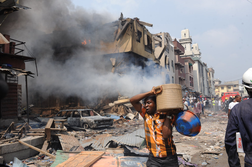 Description of . A man carries good salvaged from building stocked with fireworks on fire in Lagos on December 26, 2012. Fire ripped through a crowded neighborhood in Nigeria's largest city and wounded at least 30 people after a huge explosion rocked a building believed to be storing fireworks, officials said.   AFP PHOTO/PIUS UTOMI EKPEI/AFP/Getty Images