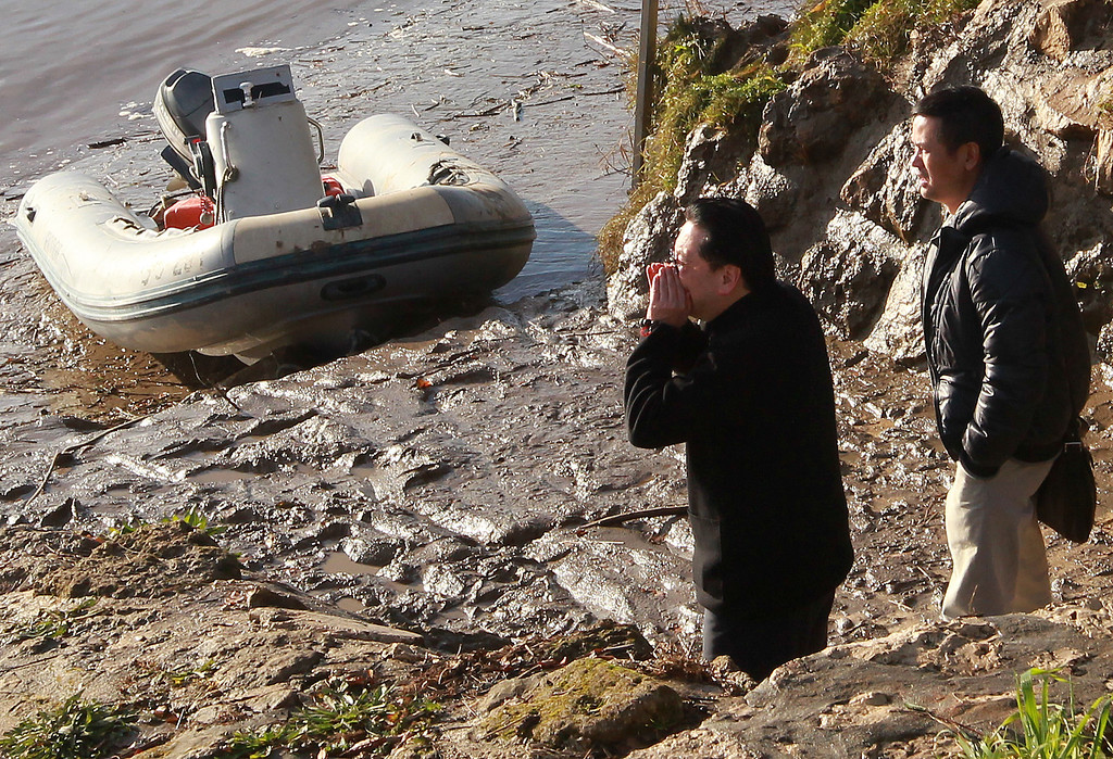 . An unidentified relative of the Chinese billionaire Lam Kok, who disappeared with his son in a helicopter crash on Friday, 20 Dec., shouts his name from the banks of the river Dordogne, in Lugon-et-l\'Ile-du-Carnay, near Bordeaux, southwestern France, Sunday, Dec.22, 2013. Chinese billionaire Lam Kok was in Bordeaux to buy the 8th-century Chateau de la Riviere and vineyard in a deal that represented the biggest ever Chinese investment in the area. (AP Photo/Bob Edme)
