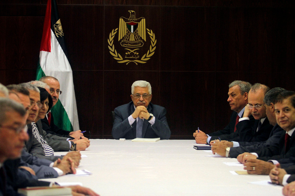 . Palestinian President Mahmoud Abbas, center, chairs a session of the Palestinian cabinet in the West Bank city of Ramallah, July 28, 2013. U.S. Secretary of State John Kerry shuttled between Israeli and Palestinian leaders for months seeking a breakthrough and announced last week that the Palestinians and the Israelis were willing to meet to discuss renewing talks. The Palestinians long refused to return to the negotiating table unless Israel agreed to several preconditions.   (AP Photo/ Xinhua, Issam Rimawi, Pool)