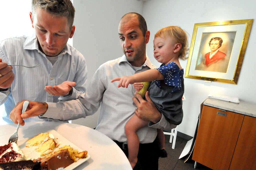 . Reid Bordson, left, and Paul Nolle, both of Bloomington, and their 18-month-old daughter Anna Bordson-Nolle, agree on their choice of yellow on the bottom tier, white for the middle and chocolate on top. (Pioneer Press: John Doman)