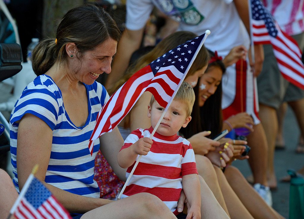 . Shayna Peeff, of Lafayette, watches her son Tommy, 15 months, wave a U.S. flag during the 30th anniversary Lamorinda Fourth of July parade and celebration on Thursday, July 4, 2013. (Jose Carlos Fajardo/Bay Area News Group)