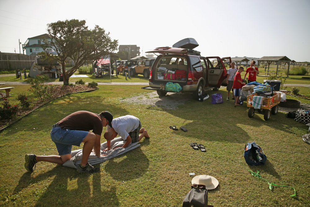 . Joey Haywood of Troy, NC. and his son Dawson Haywood fold up the families tent at a campsite before departing the KOA Campground to comply with the mandatory evacuation orders for Hatteras Island, July 3, 2014 in Rodanthe, North Carolina. A Hurricane warning has been issued for North Carolina\'s Outer Banks due to approaching Tropical Storm Arthur that is expected to gain strength and become a category 1 hurricane before it passes the area.  (Photo by Mark Wilson/Getty Images)