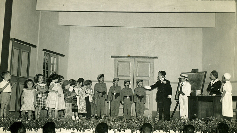 Infância em Flor - 1952  Raquel Conde ( homem vestida de preto e de barbas). Os polícias são a Lurdes Rodrigues à esquerda e o João Manuel Dyson; à direita Sara Sernadas. Tininha está com um vestido aos quadrados. A menina de branco que está de costas é a Bélita Américo Santos. Jorge