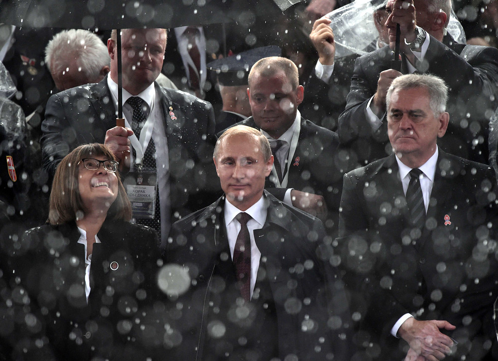 . Russian President Vladimir Putin (C) is seen trough a heavy rainfall during a military parade in Belgrade on October 16, 2014.  ANDREJ ISAKOVIC/AFP/Getty Images