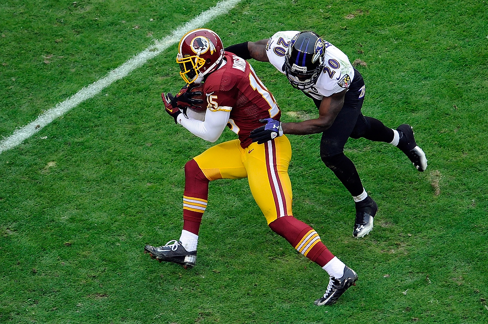 Description of . LANDOVER, MD - DECEMBER 09:  Josh Morgan #15 of the Washington Redskins avoids the tackle of Ed Reed #20 of the Baltimore Ravens during the first half at FedExField on December 9, 2012 in Landover, Maryland.  (Photo by Patrick McDermott/Getty Images)