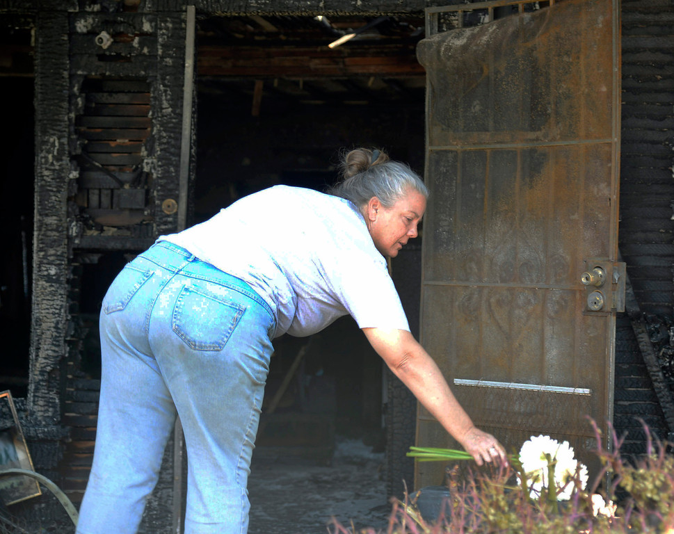 . Local neighbor and close friend Michelle Lesser lays flowers in front of her friends house  after she was killed in a house fire Saturday night in Burbank. The fire was reported at about 9:20 p.m. Saturday at 910 North Evergreen St.  Flames were showing when firefighters arrived with three people were in the house when the fire broke out. One person died in the fire, but two people got out and were transported to a hospital with non-life threatening injuries. Oct 20, 2013. Burbank CA. Photos by Gene Blevins/LA Daily News