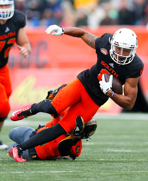 . South squad quarterback Josh Dobbs of Tennessee (11) runs the ball as North squad cornerback Aarion Penton of Missouri (11) attempts the tackle during the first half of the Senior Bowl NCAA college football game, Saturday, Jan. 28, 2017, at Ladd�Peebles Stadium, in Mobile, Ala. (AP Photo/Brynn Anderson)