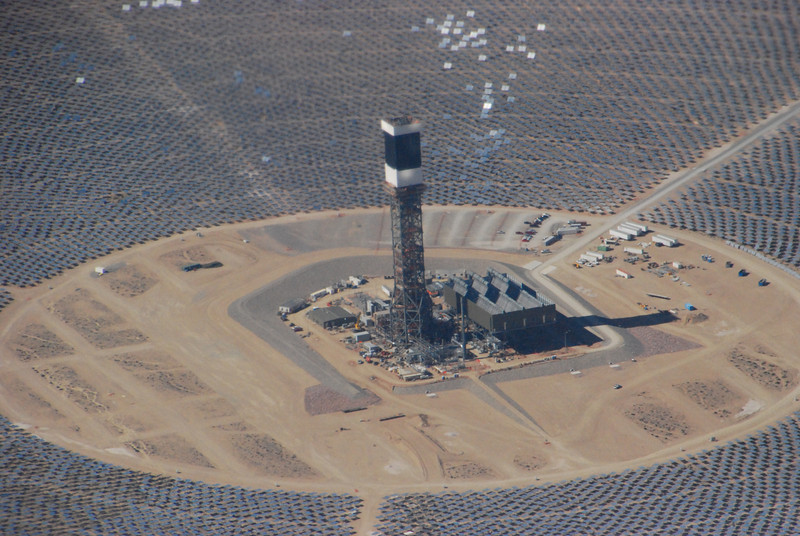 Huge field of mirrors focus sunlight onto a boiler at the top of a 450-ft tower, creating steam to generate electricity.