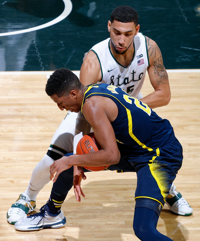 . Michigan State\'s Denzel Valentine, rear, pokes the ball away from Michigan\'s Aubrey Dawkins for a steal during the first half of an NCAA college basketball game, Sunday, Feb. 1, 2015, in East Lansing, Mich. Michigan State won 76-66 in overtime. (AP Photo/Al Goldis)