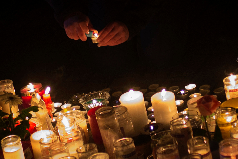 . A girl lights a candle at a memorial for victims who died in the December 14 shootings at Sandy Hook Elementary School in Sandy Hook village in Newtown, Connecticut, December 17, 2012. The two funerals on Monday ushered in what will be a week of memorial services and burials for the 20 children and six adults massacred at Sandy Hook Elementary School in Newtown, Connecticut. REUTERS/Adrees Latif