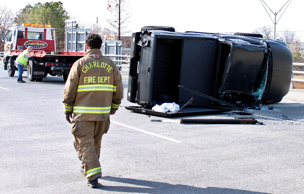 . A towing-operator works to upright the damaged truck driven by Carolina Panthers quarterback Cam Newton after the quarterback was involved in an accident, Tuesday, Dec. 9, 2014, in Charlotte, N.C. Newton was taken to the hospital.  (AP Photo/Skip Foreman)
