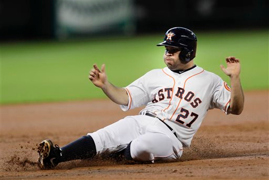 . Houston Astros\' Jose Altuve slides into third base in the first inning of a baseball game against the Minnesota Twins. (AP Photo/Bob Levey)