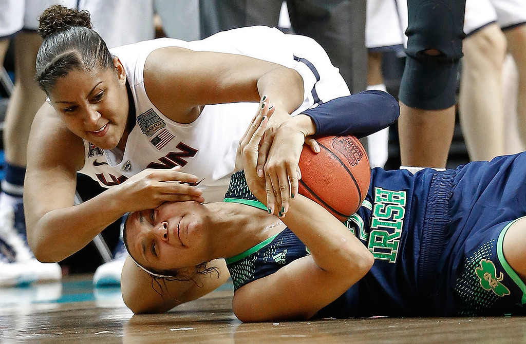 . Connecticut forward Kaleena Mosqueda-Lewis (23) and Notre Dame guard Kayla McBride (21) scramble for the ball during the first half of the championship game in the Final Four of the NCAA women\'s college basketball tournament, Tuesday, April 8, 2014, in Nashville, Tenn. (AP Photo/Mark Humphrey)