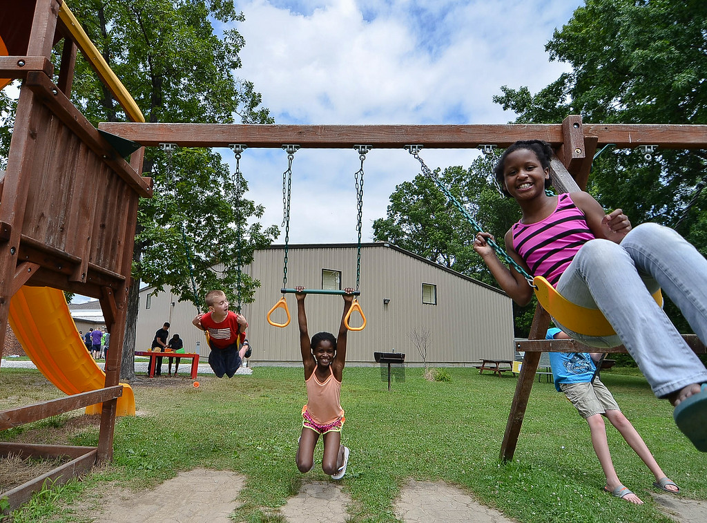 . Eric Bonzar/EBonzar@morningjournal.com Ten-year-old Jamya Phillips, foreground, swings along side her sister, Jazara Phillips, 9, and 10-year-old Keith Onacila while attending the Camp I.D.E.A.S. carnival July 16.