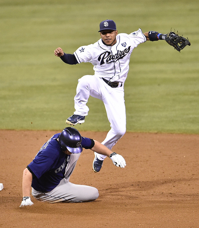 . SAN DIEGO, CA - SEPTEMBER 22:  Alexi Amarista #5 of the San Diego Padres throws over Tyler Matzek #46 of the Colorado Rockies to complete a double play during the third inning of a baseball game at Petco Park September, 22, 2014 in San Diego, California.  (Photo by Denis Poroy/Getty Images)