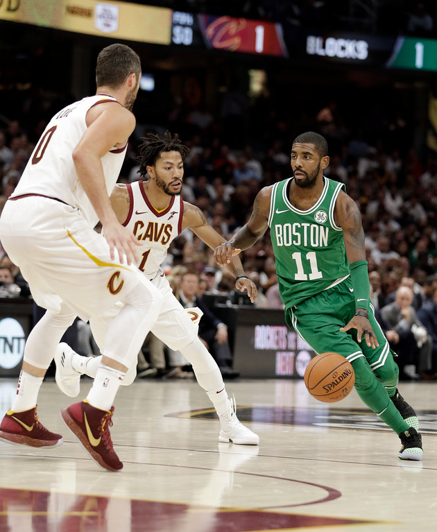 . Boston Celtics\' Kyrie Irving (11) drives past Cleveland Cavaliers\' Kevin Love (0) and Derrick Rose (1) in the first half of an NBA basketball game, Tuesday, Oct. 17, 2017, in Cleveland. The Cavaliers won 102-99. (AP Photo/Tony Dejak)