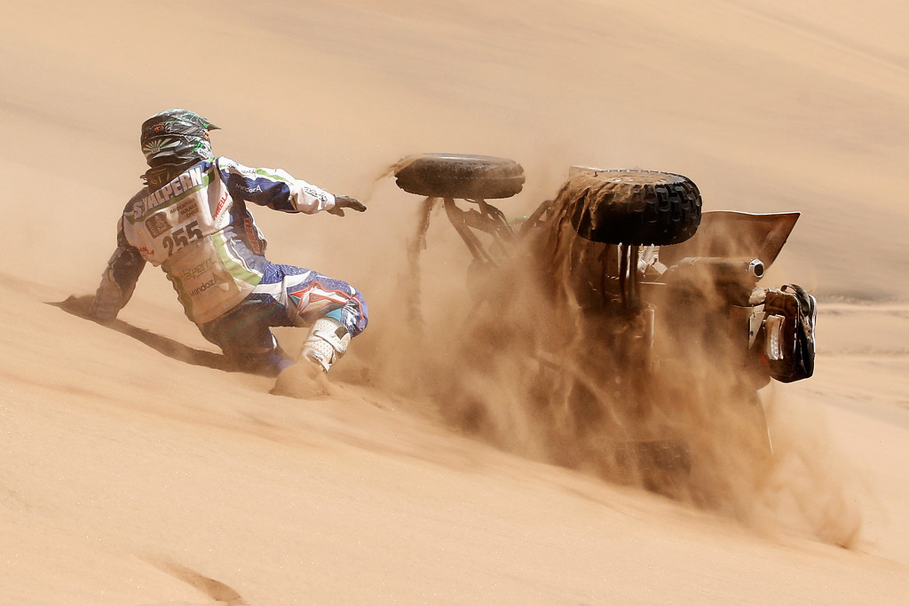 . COPIAPO, CHILE - JANUARY 07:  #255 Sebastian Halpern of Argentina riding for Mendoza Espiritu Grande chases his quad as it rolls down the sand dune during day 4 of the Dakar Rallly on January 7, 2015 between Chilecito in Argentina to Copiapo, Chile.  (Photo by Dean Mouhtaropoulos/Getty Images)