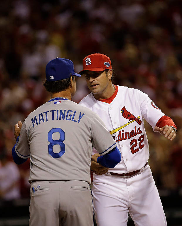 . Los Angeles Dodgers manager Don Mattingly (8) speaks with St. Louis Cardinals manager Mike Matheny (22) before the first inning of Game 1 of the National League baseball championship series Friday, Oct. 11, 2013, in St. Louis. (AP Photo/David J. Phillip)