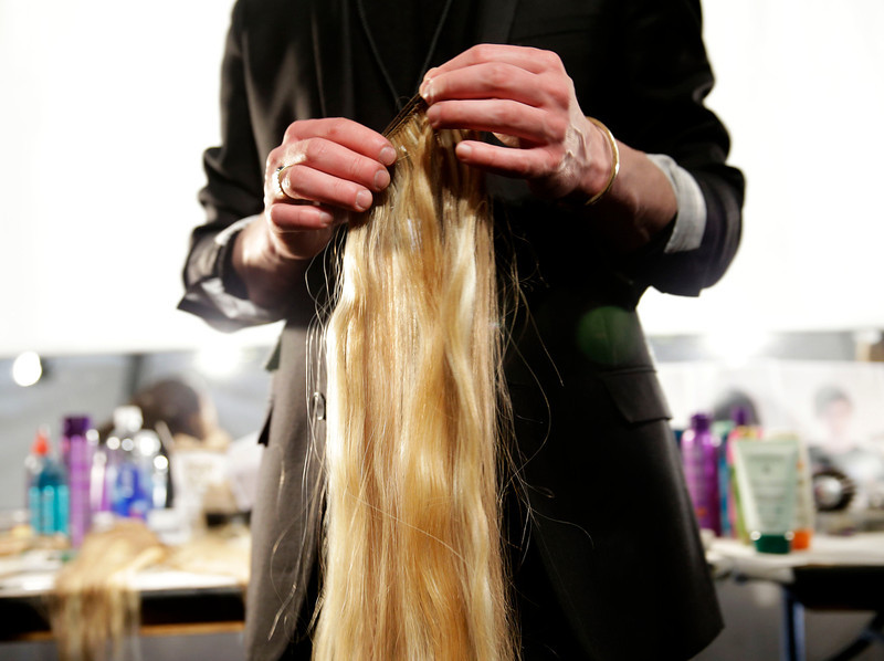 . A man holds hair extensions backstage before the Fall 2014 Creatures of the Wind collection is modeled during Fashion Week in New York, Thursday, Feb. 6, 2014.  (AP Photo/Seth Wenig)