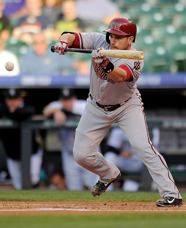 . Arizona Diamondbacks Miguel Montero hits a bunt single in the first inning of a baseball game against the Colorado Rockies on Thursday, June 5, 2014, in Denver. (AP Photo/Chris Schneider)