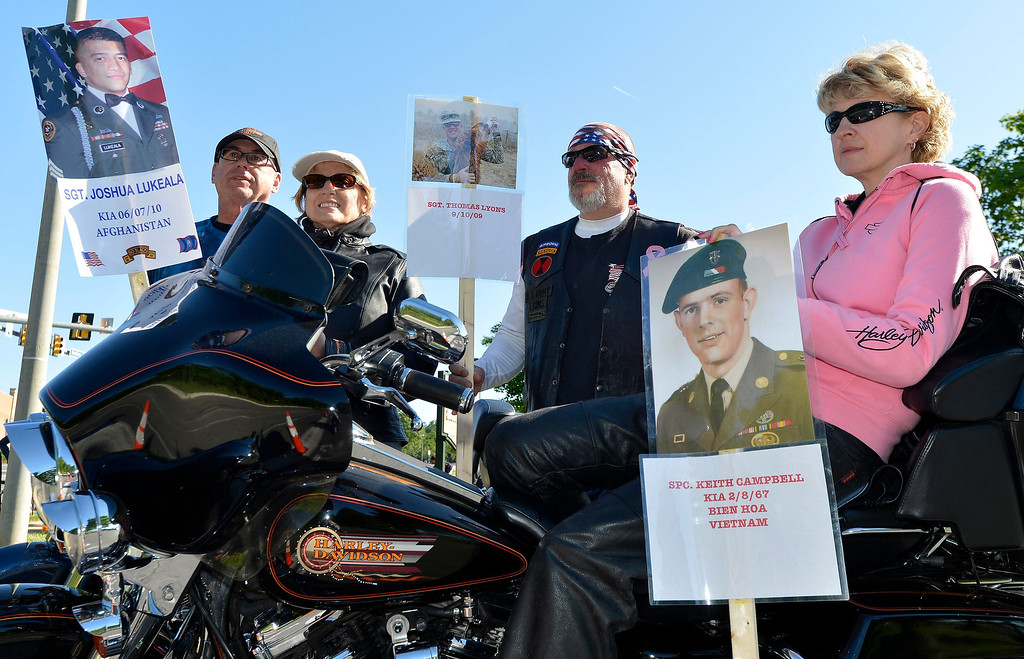 . Motorcycle riders, from left, Doug and Diane Frame and Walter and Deanna Lyons of Manassas, Virginia, hold posters of fallen U.S. military personnel as they await the arrival of hundreds of thousands of motorcyclists in Fairfax, Virginia, gathering on Memorial Day weekend for the 26th Annual Rolling Thunder Rally to remember POWs and MIAs from America\'s wars, in Washington, May 26, 2013.   REUTERS/Mike Theiler