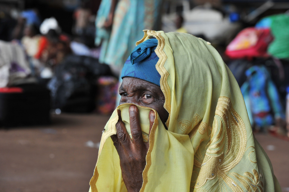 """. A woman covers her mouth with her head scarf as displaced Central African and Chadian Muslims fleeing attacks by Christian extremist militias sit in a hangar at the airport in Bangui on January 30, 2014, waiting to leave Central Africa with the aid of the International Organization for Migration (IOM). Rudimentary weapons taken from Christian extremist militias by French troops in the capital of the Central African Republic were piled up on the ground, near the body of a young man whose ears were ripped off. \""""He was a Muslim from here, named Abaka. They killed him in the courtyard of his house,\"""" a Christian neighbour, Benjamin, told AFP. \""""They\"""" referred to \""""anti-balaka\"""" (anti-machete) vigilantes who fiercely target Muslims in Bangui on the pretext of hunting down ex-rebels from the Seleka coalition. (ISSOUF SANOGO/AFP/Getty Images)"""