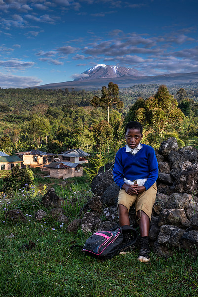 A little boy on his way to school. Mount Kilimanjaro in the background.  Tanzania, 2019