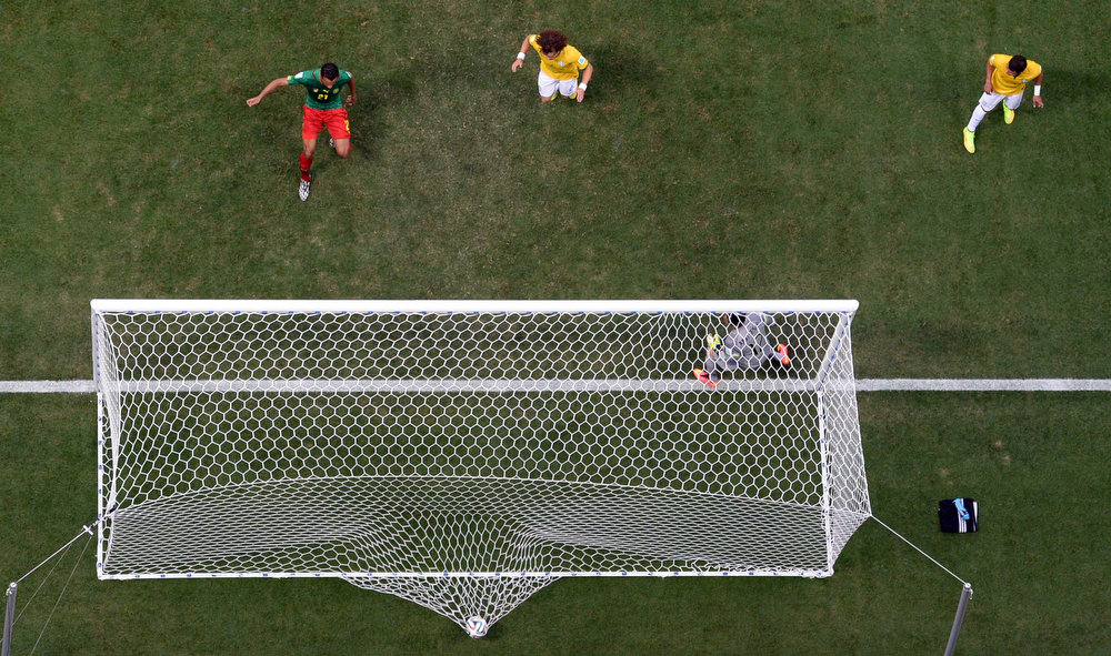 . Cameroon\'s Joel Matip, left, scores his side\'s first goal during the group A World Cup soccer match between Cameroon and Brazil at the Estadio Nacional in Brasilia, Brazil, Monday, June 23, 2014. (AP Photo/Francois Xavier Marit, pool)
