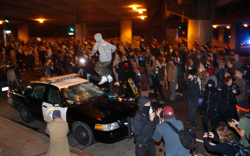 . A man jumps on a vandalized CHP squad car on Telegraph Avenue under the Highway 24 overpass in Oakland, Calif., Sunday evening, Dec. 7, 2014, during a second consecutive night of civil disobedience protesting the killings of two unarmed black men by police in Ferguson, Mo., and New York. (Karl Mondon/Bay Area News Group)