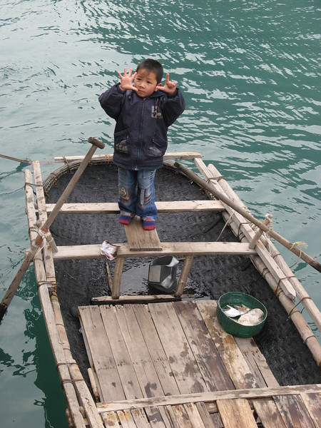 Boy selling shells showing how old he is (7).
