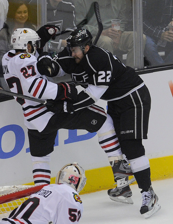 . Kings#22 Trevor Lewis checks Blackhawks#27 Johnny Oduya into the boards in the first period. The Kings played the Chicago Blackhawks in the 3rd game of the Western Conference Finals. Los Angeles, CA 6/4/2013(John McCoy/LA Daily News4