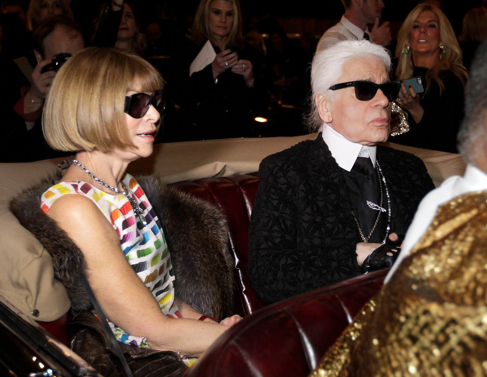 ". Anna Wintour, left, the english editor-in-chief of American Vogue and designer Karl Lagerfeld sit in a vintage car as they wait to view a movie short of Coco Chanel\'s return to fashion after closing her house during WWII before the start of Chanel\'s Metiers d\'Art fashion show, Tuesday, Dec. 10, 2013, in Dallas. For more than a decade, designer Karl Lagerfeld has picked a city linked to the house for the theme of the show staged each December to highlight the work of its artisans. Fashion house founder Gabrielle ""Coco\"" Chanel visited Dallas in 1957 at the invitation of Stanley Marcus, who led Neiman Marcus, the Dallas-based luxury retailer founded by his family. (AP Photo/Tony Gutierrez)"