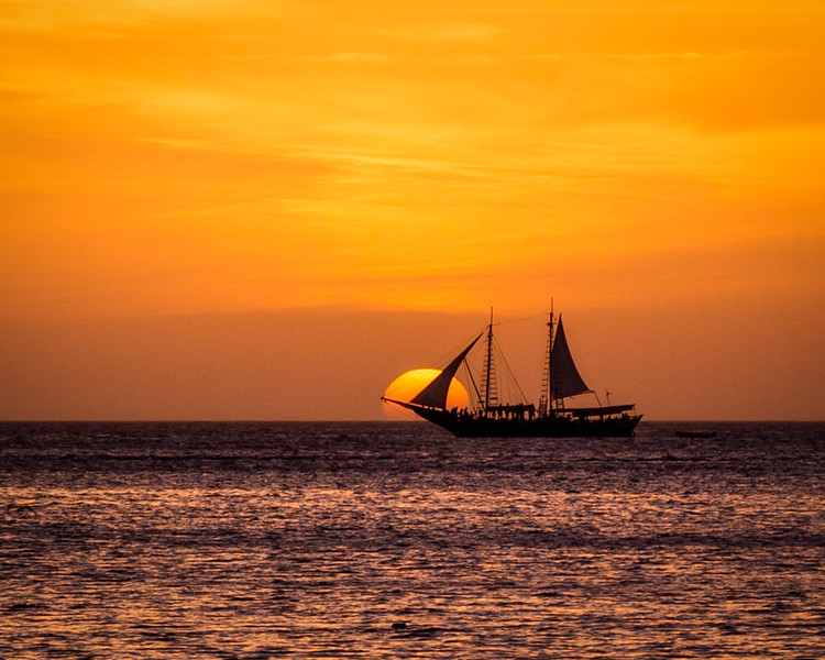 A yellow and orange sunset into the water with a sailboat sailing through the scene.