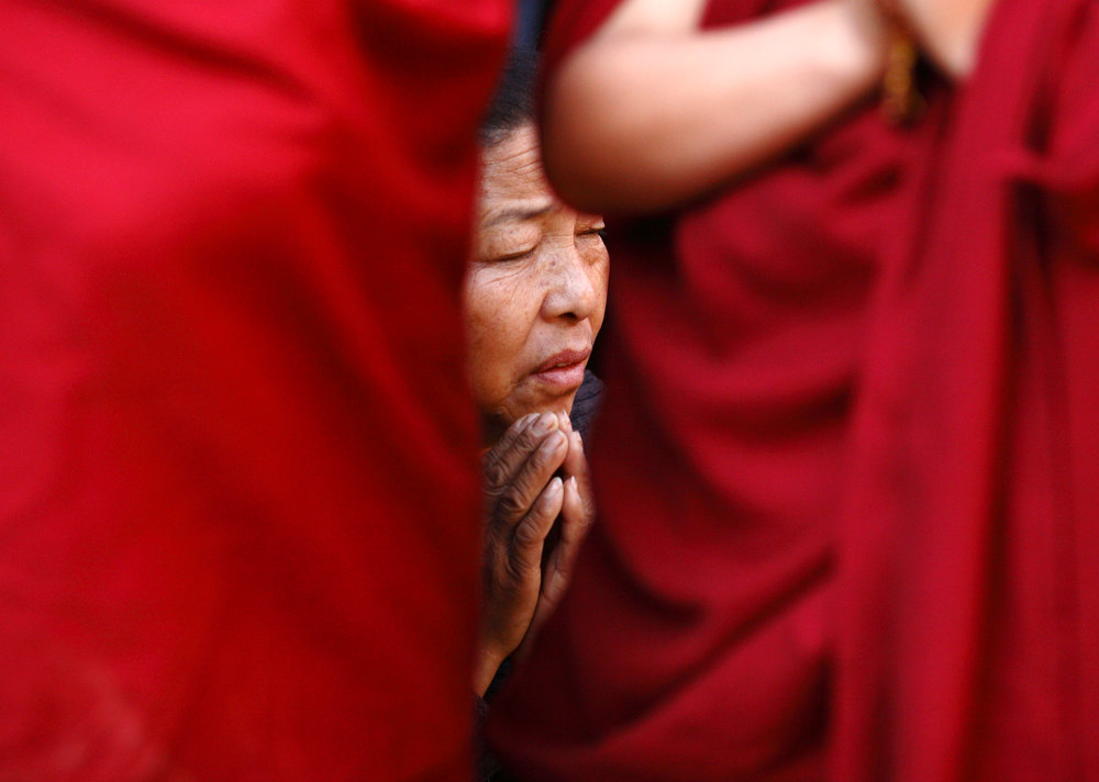 Description of . A Tibetan woman prays during a function organized at the Tibetan monastery in Boudhanath Stupa to mark the third day of New Year or
