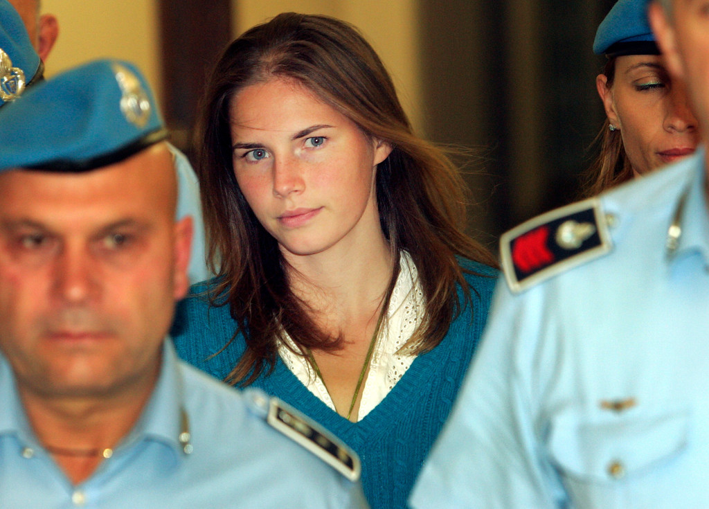 . In this Sept. 26, 2008 file photo, American murder suspect Amanda Knox is escorted by Italian penitentiary police officers to Perugia\'s court at the end of a hearing, central Italy.    (AP Photo/Pier Paolo Cito, files)