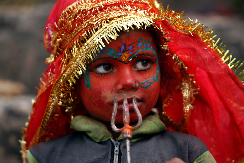 . Indian child dressed like Hindu goddess Kali stands at the steps leading to a Hindu temple during Navaratri, or nine nights festival, in Jammu, India, Sunday, Oct. 13, 2013.(AP Photo/Channi Anand)