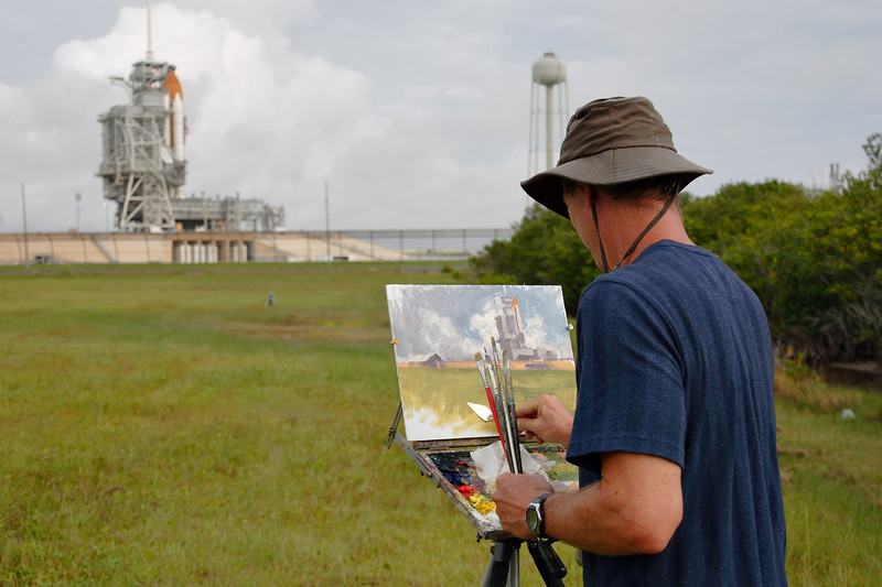 An artist paints a scene of Atlantis on the pad during remote camera setup in the morning.