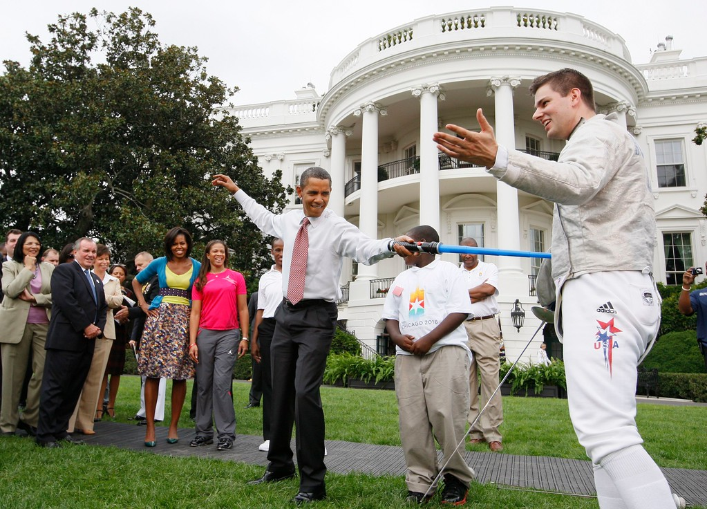 . President Barack Obama uses a light saber as he watches a demonstration of fencing with Tim Morehouse who won a silver medal in Men\'s Saber Fencing at the Beijing Olympics, Wednesday, Sept. 16, 2009, during an event supporting Chicago\'s 2016 host city Olympic bid, on the South Lawn of the White House in Washington. At rear is Chicago Mayor Richard Daley, and first lady Michelle Obama. (AP Photo/Charles Dharapak)