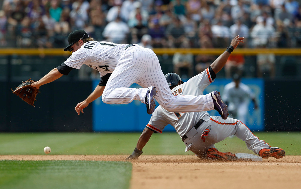 . Colorado Rockies shortstop Josh Rutledge, front, tumbles while trying to field an errant throw as San Francisco Giants\' Tony Abreu slides safely back into second base in the fifth inning of a baseball game in Denver on Sunday, June 30, 2013. The play started when the Giants\' Buster Posey grounded out to drive in a run but Rockies first baseman Jordan Pacheco tried to throw out the Giants\' Abreu as he leaned off second base.  (AP Photo/David Zalubowski)
