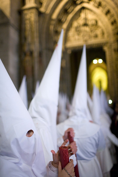 Row of hooded penitents entering Seville's Cathedral, Spain