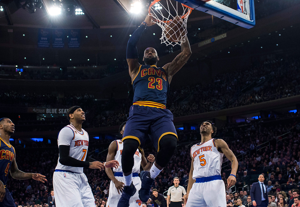 . Cleveland Cavaliers\' LeBron James (23) dunks next to New York Knicks\' Carmelo Anthony (7) and Courtney Lee (5) during the first half of an NBA basketball game, Saturday, Feb. 4, 2017, in New York. (AP Photo/Andres Kudacki)